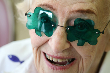 smiling woman with shamrock glasses