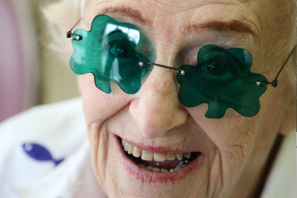 photo of smiling senior woman with shamrock glasses
