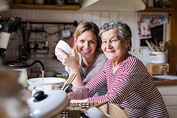 woman helping senior woman wash dishes